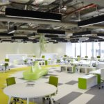Designer office space featuring bright and vibrant colours. the ceiling is industrial looking, showing off the ductwork and other services.